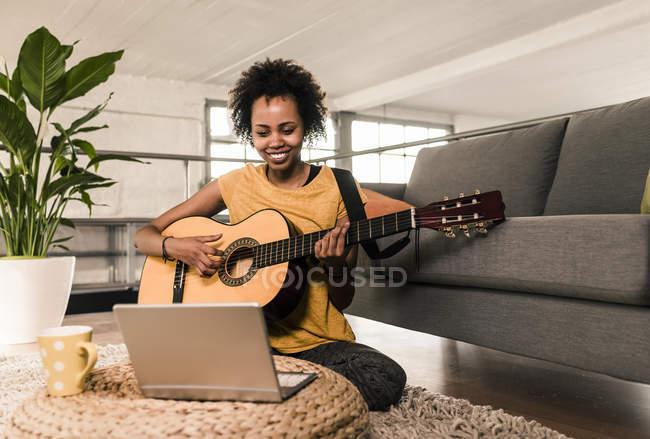 Женщина дома играет на гитаре — стоковое фото