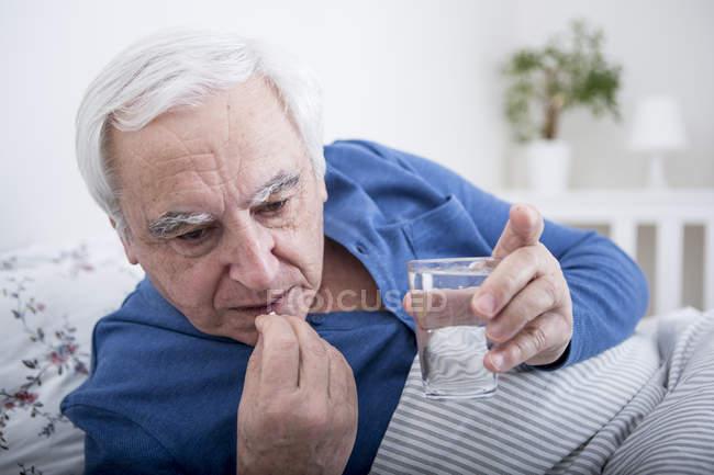 Sick man taking tablets — Stock Photo