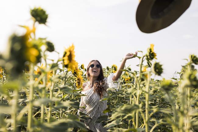 Femme debout dans le champ de tournesol — Photo de stock