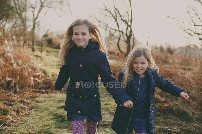 Two sisters running on meadow — Stock Photo