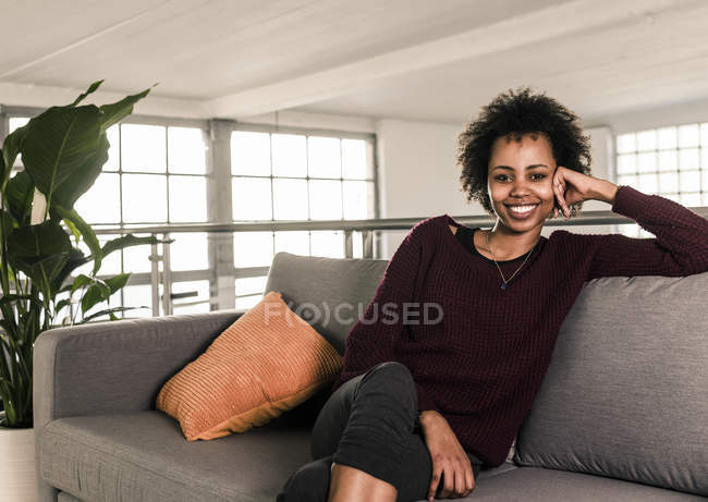 Woman sitting on couch — Stock Photo