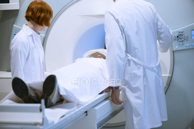 Doctors preparing patient for magnetic resonance imaging — Stock Photo