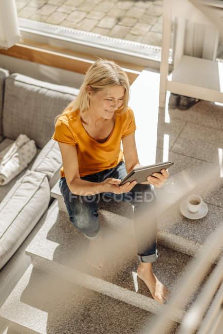 Femme assise sur les escaliers avec une tasse de café — Photo de stock