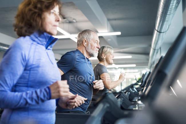 Senioren arbeiten auf Laufbändern — Stockfoto