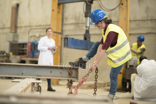 Фабрика працівник потягнувши залізний ланцюг — стокове фото