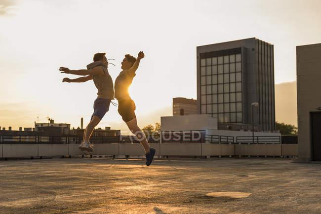 Amici salti di gioia al tramonto — Foto stock