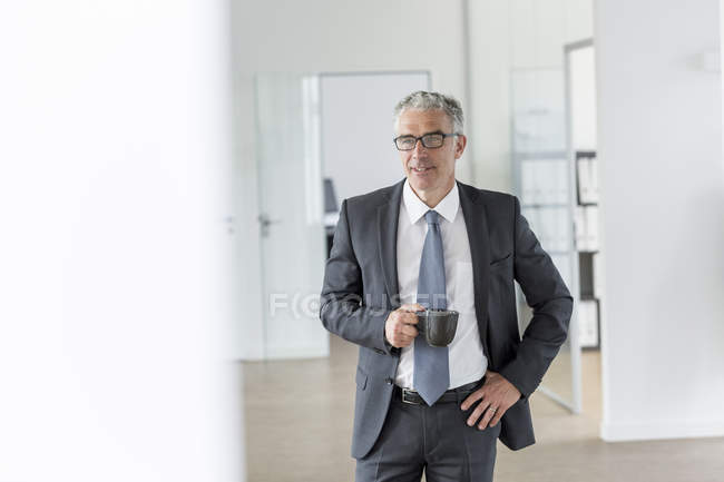 Businessman holding cup of coffee — Stock Photo