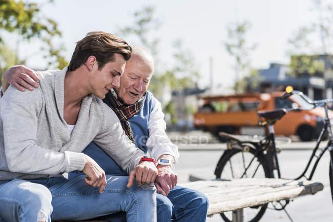 Senior man and adult grandson on bench — Stock Photo