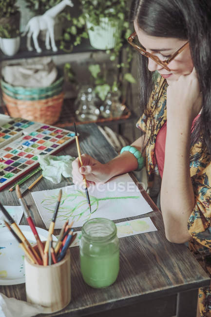 Woman painting plants with watercolors — Stock Photo