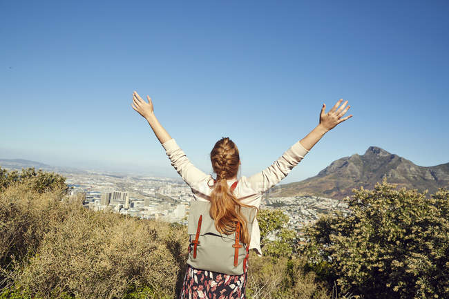 Woman with raised arms overlooking city — Stock Photo