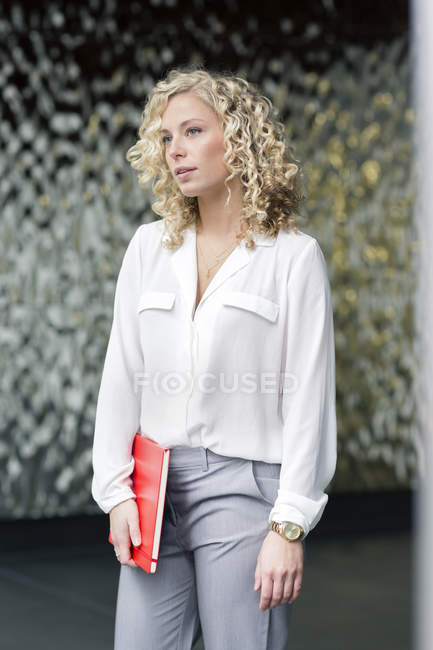 Portrait of attractive blond businesswoman with notebook waiting in a foyer — Stock Photo