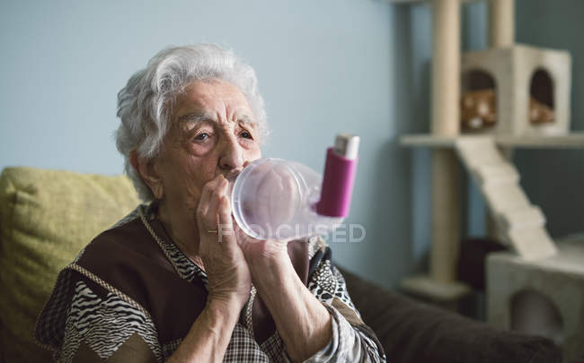 Senior woman using inhaler — Stock Photo