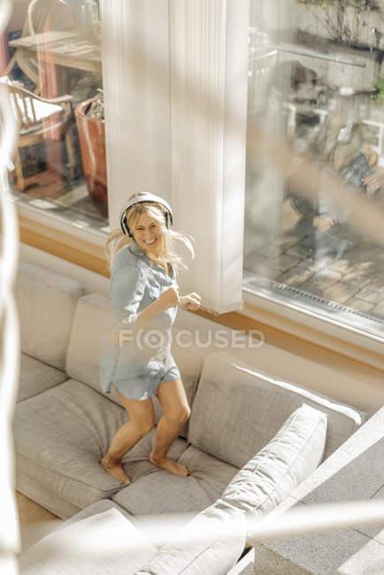 Femme portant un casque dansant sur le canapé — Photo de stock