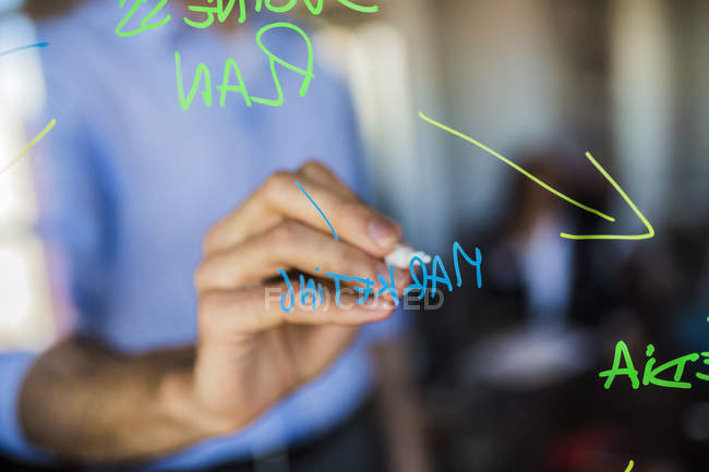 Businessman writing on glass wall — Stock Photo