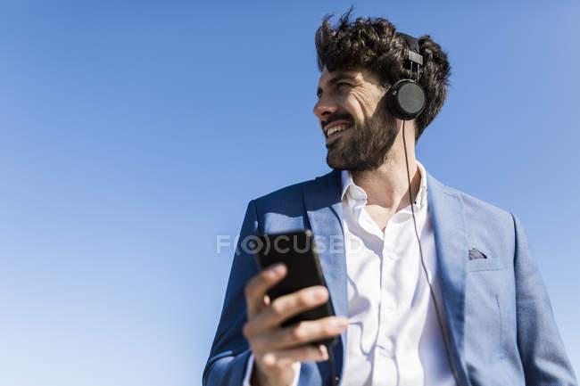 Businessman with smartphone wearing headphones — Stock Photo