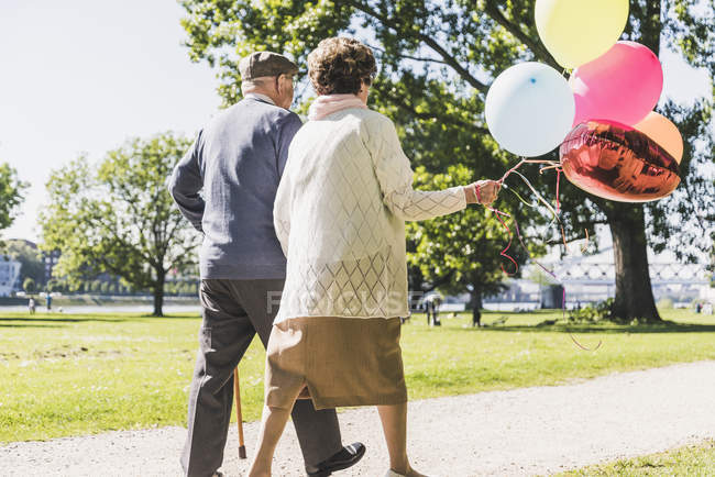 Senior couple with balloons strolling in park — Stock Photo