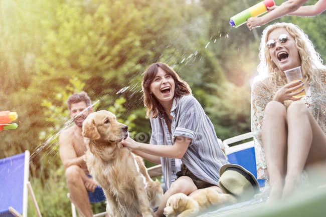 Amici felici con il cane si diverte con una pistola ad acqua — Foto stock