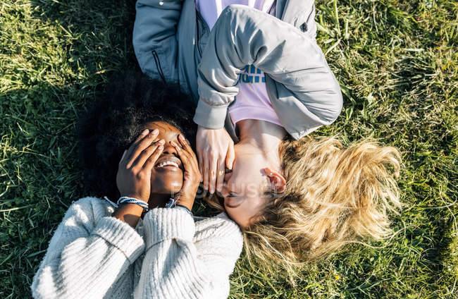 Friends telling secrets lying in grass — Stock Photo