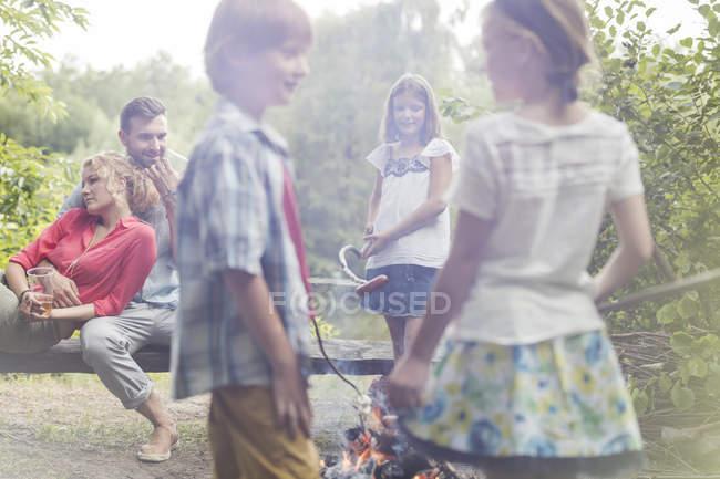 Famiglia caucasica arrostire salsicce al campfire — Foto stock