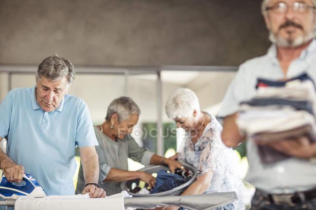 Seniors ironing clothes — Stock Photo
