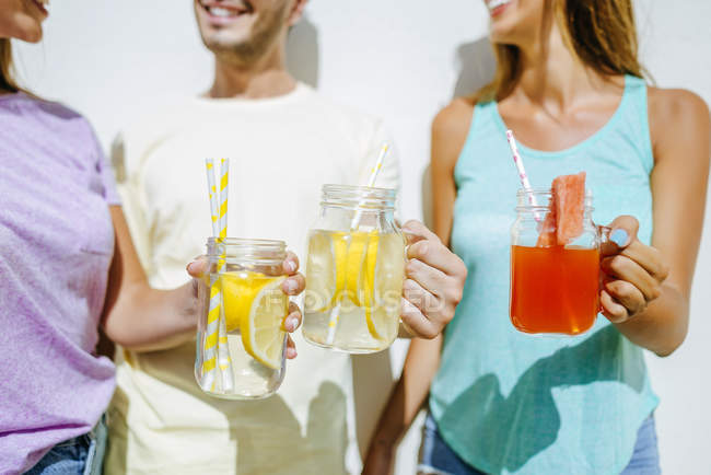 Friends holding refreshing drinks — Stock Photo
