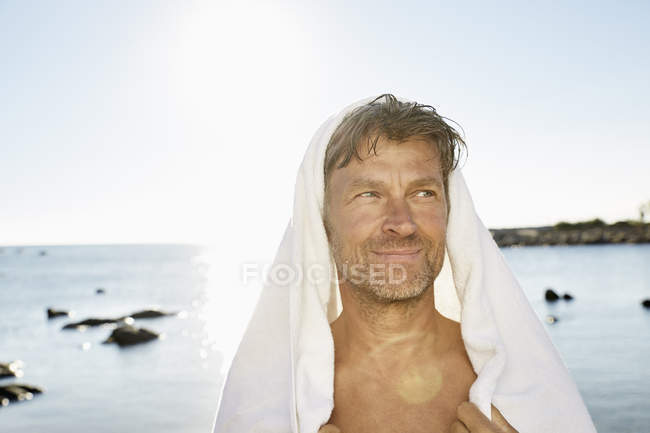 Man with towel in front of sea — Stock Photo