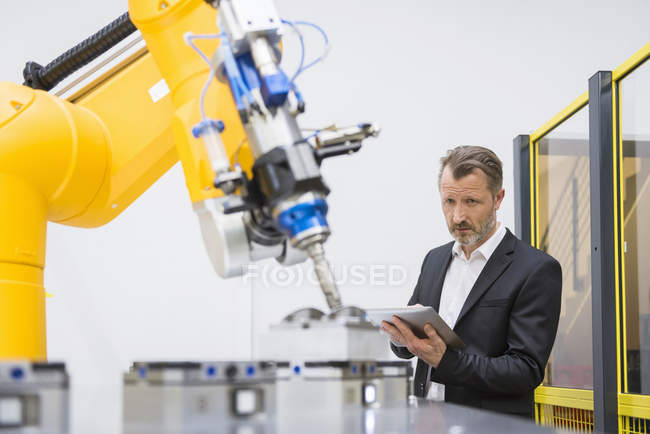 Robot industriel contrôle homme d'affaires — Photo de stock