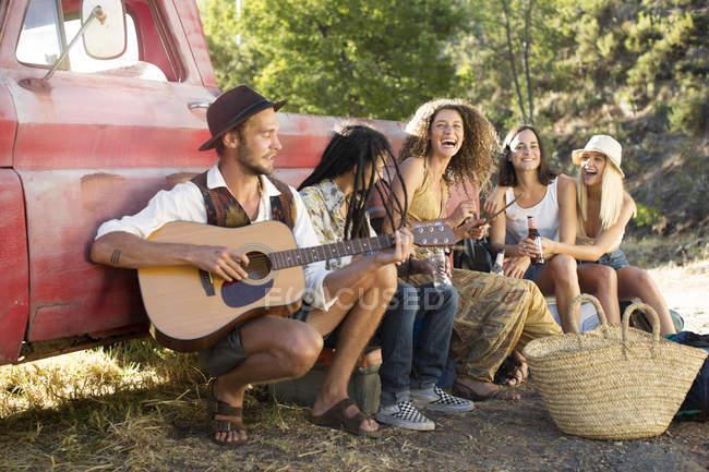 Счастливые молодые люди сидят рядом с фургоном и веселятся — стоковое фото