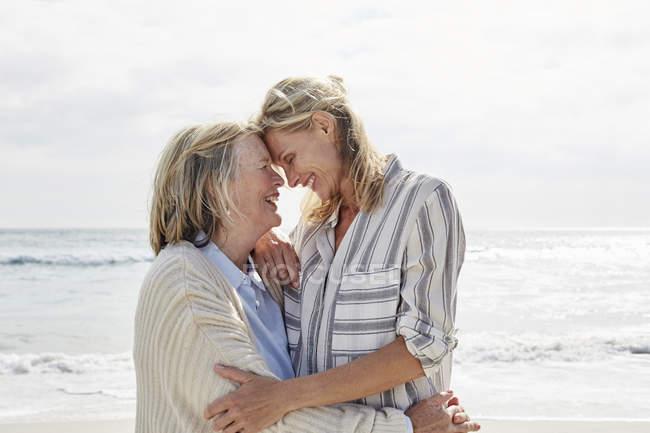 Старшая женщина и взрослая дочь стоят на пляже — стоковое фото