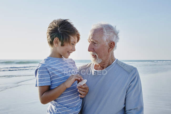 Grandfather with grandson on beach — Stock Photo