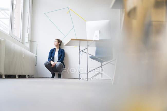 Businesswoman crouching on floor — Stock Photo