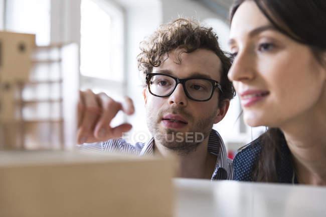 Uomo e donna discutono il modello architettonico — Foto stock