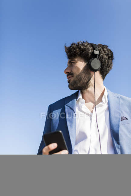 Бизнесмен со смартфоном в наушниках — стоковое фото