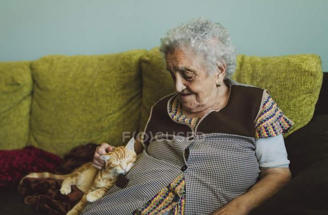 Femme assise sur le canapé caressant chat — Photo de stock