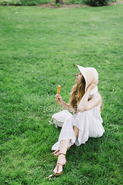 Жінка сидить на луг і їдять popsicle — стокове фото
