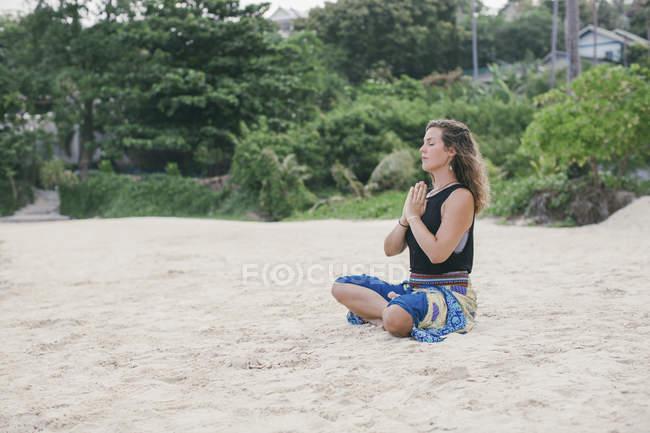 Женщина практикует йогу на пляже — стоковое фото