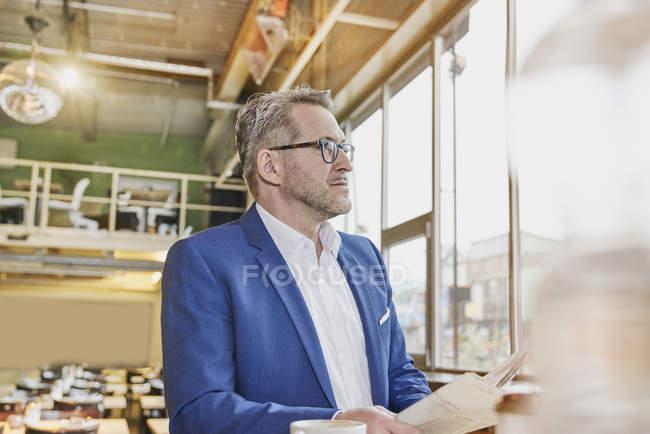 Uomo d'affari in piedi in caffè con giornale — Foto stock