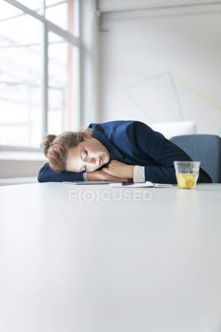Businesswoman fallen asleep over digital tablet — Stock Photo