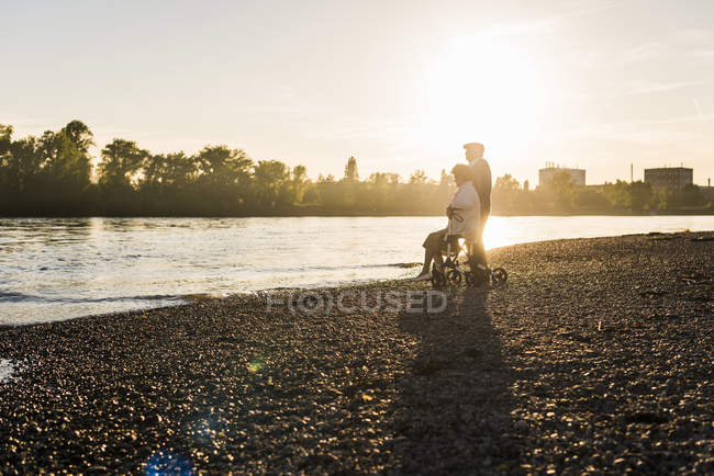 Couple with wheeled walker on the beach — Stock Photo