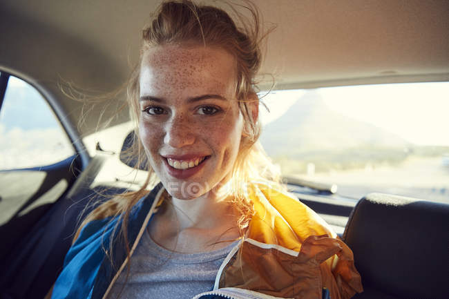 Woman on back seat of car — Stock Photo