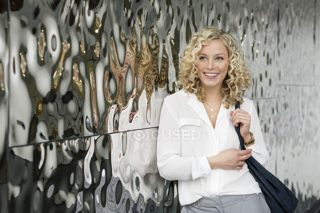 Portrait of smiling young  businesswoman leaning against mirrored wall — Stock Photo