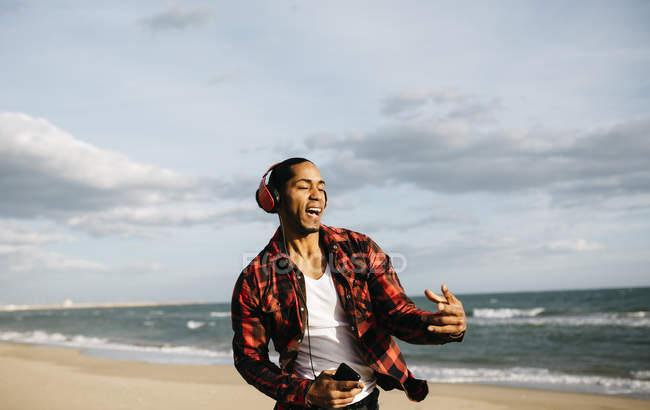 Homem na praia cantando e dançando — Fotografia de Stock