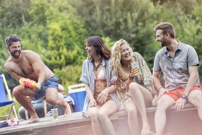 Amici felici divertendosi con una pistola ad acqua su un molo — Foto stock