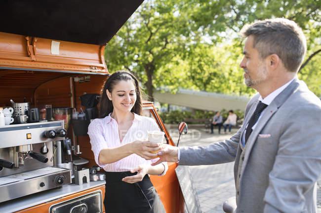 Businessman buying take away coffee — Stock Photo