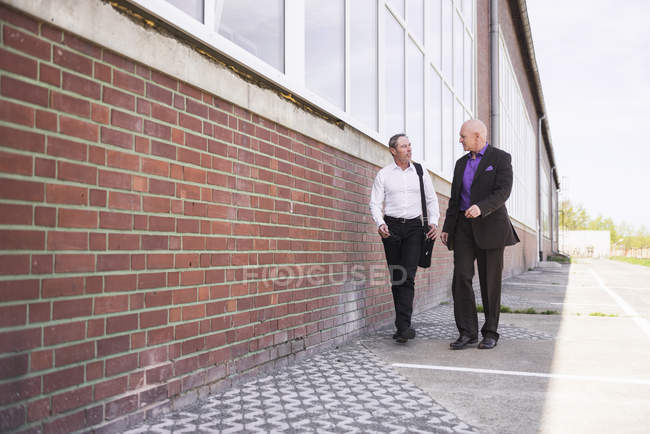 Men walking along factory building — Stock Photo