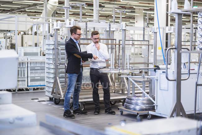 Men talking in factory shop floor — Stock Photo