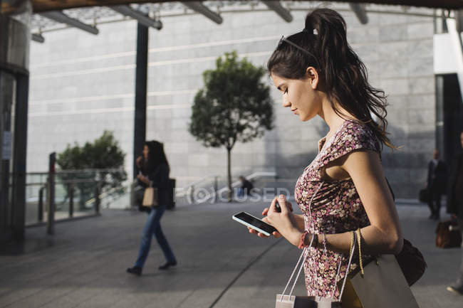 Woman using cell phone in city — Stock Photo
