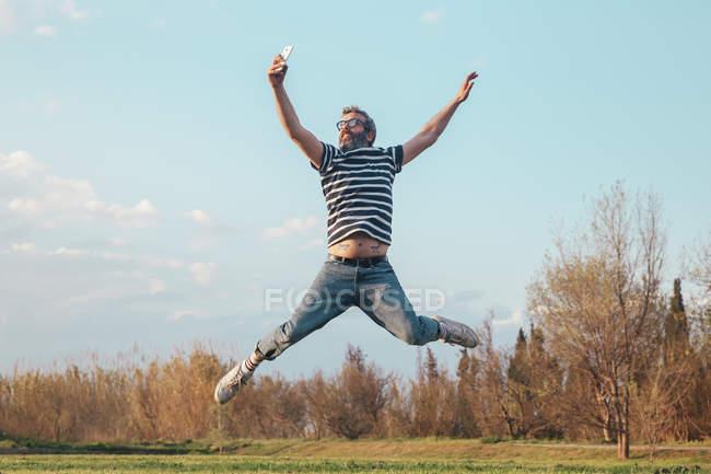 Homme sautant prendre des photos avec smartphone — Photo de stock