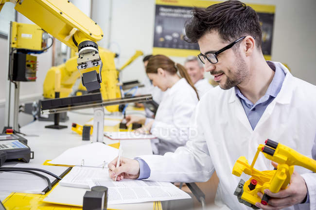 Engineer in factory holding model of an industrial robot taking notes on clipboard — Stock Photo