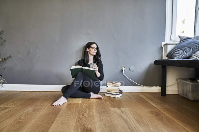 Woman with books sitting on floor — Stock Photo